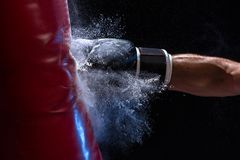 Close-up hand of boxer at the moment of impact on punching bag over black background. Strength and motivation. Studio shot stock images
