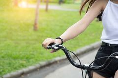 Close up hand brake bike, young woman riding bicycle in park. royalty free stock photos