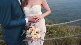 Close up hand of bride strokes hand of groom, sea on background, slow motion stock video