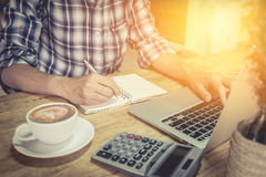 Close up hand of business man using laptop computer and write on. Notebook with cup of coffee and calculator on wooden desk outdoor office with morning light Royalty Free Stock Photography