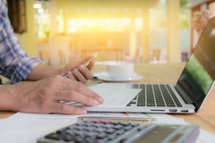 Close up hand business man using laptop and graph and smart phon. E for sync data with laptop on wooden desk with morning light Royalty Free Stock Image