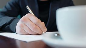 Close up hand of businessman signing contract with silver ballpen on the table with cup of coffee. stock video