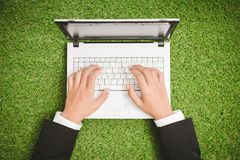 Close up hand businessman working  on laptop. On green grass Stock Image