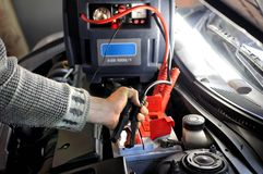 Close up of hand charging car battery with electricity trough jumper cables on the background of the charger stock photography