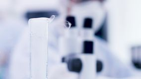 Close up hand of chemist scientist taking a bottle of smoking blue fluid. Chemist in coverall equipment stock footage