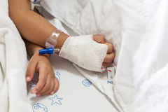 Close up of hand children sick sleeping on the bed. To the brine on hand for treated at hospital stock photo