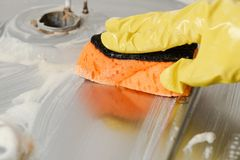 Close-up of hand cleaning gas cooker in kitchen. Close-up of hand in yellow glove cleaning gas cooker in kitchen. Removal of dirty foam with orange sponge from royalty free stock images