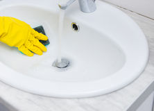 Close up on hand cleaning sink with sponge Royalty Free Stock Photography