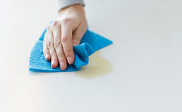 Close up of hand cleaning table surface with cloth. People, housework and housekeeping concept - close up of woman hand cleaning spot from table surface with Royalty Free Stock Images