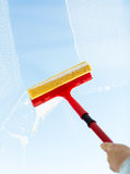 Close up of hand cleaning window with sponge Stock Photo