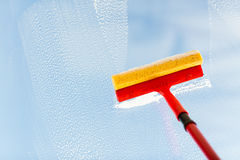 Close up of hand cleaning window with sponge Royalty Free Stock Photo