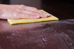 Close up of  hand cleaning wooden table with furniture polish. Using yellow sponge for cleaning dusty wood. House  cleaning and ho Stock Image