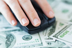 Close up of hand with computer mouse on money Royalty Free Stock Photo