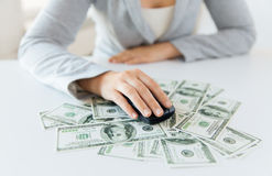 Close up of hand with computer mouse on money Stock Photo