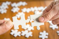 Close up of hand connecting jigsaw puzzle with wooden background, business solutions Stock Image