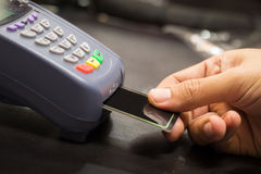 Close Up Of Hand With Credit Card Swipe Through Terminal. For Sale In Store : Selective Focus stock photo