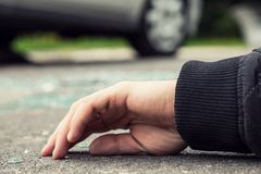 Close-up of a hand of dead person after collision with a car on. The road stock images