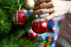 Close up hand decorating the chrismas tree with beautiful red ball toy f stock photos