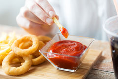 Close up of hand dipping french fries into ketchup. Fast food, people and unhealthy eating concept - close up of hand with deep-fried squid rings, dipping french stock photo