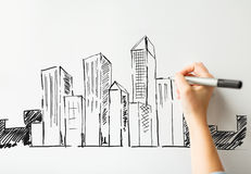 Close up of hand drawing city on white board Stock Images