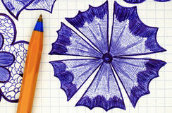 Close-up of hand drawn flower on sheet of checkered paper with o Stock Photography
