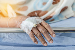 Close up hand of elderly patient with intravenous catheter for injection plug in hand. During lying in hospital ward room Royalty Free Stock Images