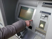 Close up of hand entering pin at an ATM.Female arms, ATM - entering pin.Woman using banking machine Royalty Free Stock Photo