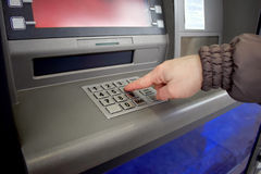 Close up of hand entering pin at an ATM. Female arms, ATM - entering pin.Woman using banking machine Stock Image
