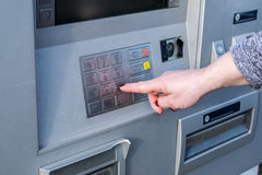 Close up of hand entering pin at an ATM. Female arms, ATM - entering pin.Woman using banking machine Stock Photos