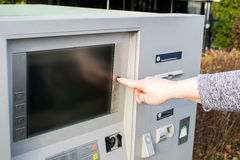 Close up of hand entering pin at an ATM. Female arms, ATM - entering pin.Woman using banking machine Royalty Free Stock Image