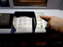 Close up of hand entering pin at an ATM. Female arms, ATM - entering pin.Woman using banking machine. Close up of hand entering pin at an ATM. Female arms, ATM Stock Image