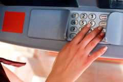 Close up of hand entering pin at an ATM. Finger about to press a Stock Photos
