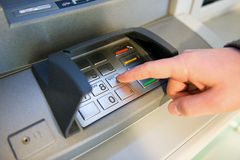Close-up of hand entering PIN code on ATM machine keypad. Royalty Free Stock Image