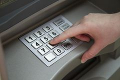 Close-up of hand entering PIN pass code on ATM bank machine keypad. Close-up of handenting PIN passcode on ATM bank machine keypad. Female hand finger presses royalty free stock photos