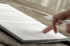 Close up of hand with fancy pen on document Royalty Free Stock Photo
