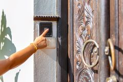 Close up of hand female pushing the button to open the door at the front home Royalty Free Stock Image