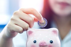 Close up hand female stack euro coins putting in piggy bank. Saving money concept royalty free stock photo