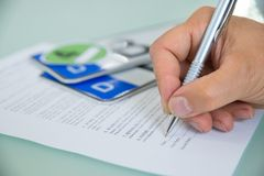 Close-up of hand filling car sale contract form Stock Photography