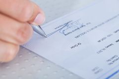 Close-up of hand filling cheque Stock Photography