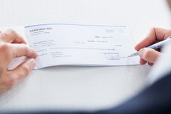 Close-up of hand filling cheque Stock Photos