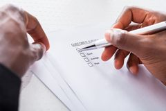 Close-up of hand filling form Stock Photo