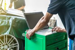 Close up hand finger of repairman touch laptop or computer notebook interfaced with car for repair during work investigate problem. Program and electric check stock photography