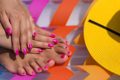 Close-up hand and foot on a pink air mattress in swimming pool. Stock Photos