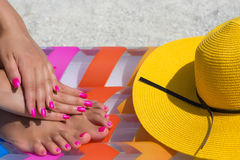 Close-up hand and foot on a pink air mattress in swimming pool. Royalty Free Stock Photo
