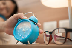 Close up of hand of girl turns off the alarm clock. Royalty Free Stock Images