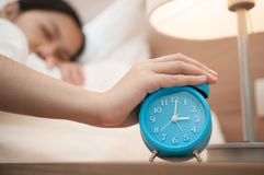 Close up of hand of girl turns off the alarm clock. Royalty Free Stock Photo