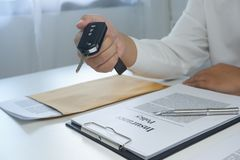 Close-up hand giving a car key after signing a document stock photos