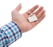 Close-up of hand giving a key ring with house isolated on white Royalty Free Stock Image