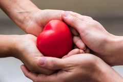 Close up hand giving red heart as heart donor. Valentine day of love concept. Medical ventilator and heart donator charity. Sign