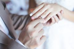 Close up hand groom couple put giving the Wedding Ring on bride. stock image
